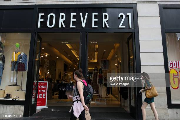 Shoppers walk past a branch of Forever 21 store in central London.