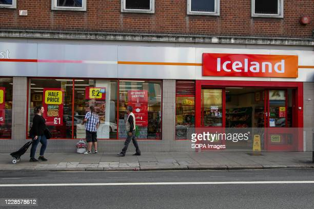 Shoppers walk past a branch of Iceland supermarket in London.