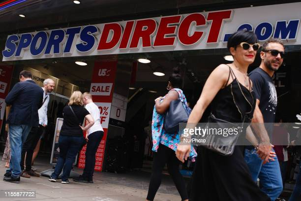 Shoppers walk past a branch of sporting goods retailer Sports Direct owned by high street tycoon Mike Ashley on Oxford Street in London England on...