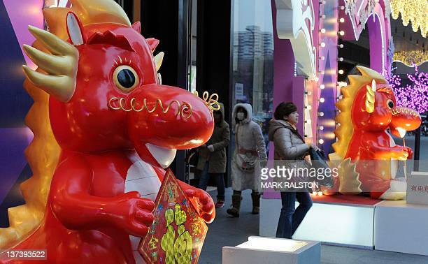 Shoppers walk past a Chinese Spring Festival 'Year of the Dragon' display at a shopping center in Beijing on January 20 2012 The Chinese New Year...