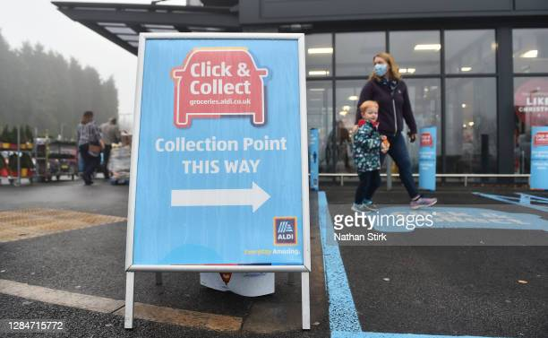 Shoppers walk past a click and collect sign as German supermarket chain, Aldi is to extend its trial of click and collect to up to more than 200...