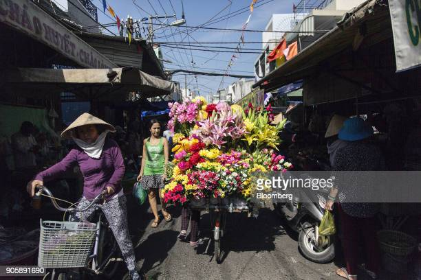 Shoppers walk past a flower vendor on a bicycle at a street market in Ho Chi Minh City Vietnam on Friday Jan 12 2018 A global trade recovery and...