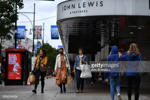 Shoppers walk past a John Lewis store in Oxford Street, central London on July 2, 2020.