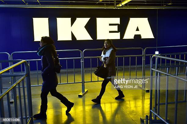Shoppers walk past a logo of Ikea at its store in Gwangmyeong south of Seoul on December 18 2014 Global furniture giant Ikea opened its first store...