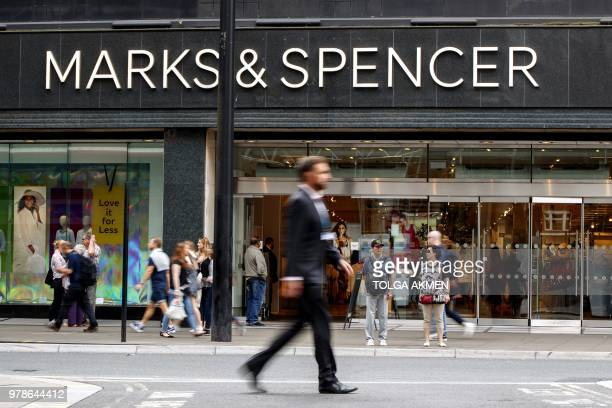 Shoppers walk past a Marks Spencer shop on Oxford Street in central London on June 19 2018 Major UK retailers are increasingly facing tough times in...