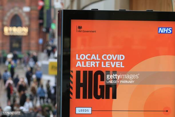 Shoppers walk past a NHS sign displaying the Local Covid Alert Level as 'high' in the centre of Leeds, West Yorkshire, northern England, on October...