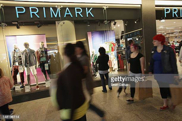 Shoppers walk past a Primark clothing store a day after the store's opening on July 12 2012 in Berlin Germany Primark is expanding aggressively in...