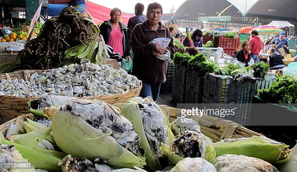 Shoppers walk past a produce stand containing huitlacoche at Mexico City's wholesale market August 6 2011 The fungus known as huitlacoche in Mexico...