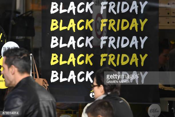 Shoppers walk past a promotional sign for 'Black Friday' sales in Rennes western France on November 24 2017 Black Friday is a sales offer originating...