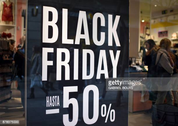 Shoppers walk past a promotional sign for 'Black Friday' sales in Madrid on November 24 2017 Black Friday is a sales offer originating from the US...