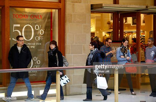 Shoppers walk past a retail shop offering Black Friday deals at Somerset Collection shopping mall on November 29 2013 in Troy Michigan Black Friday...