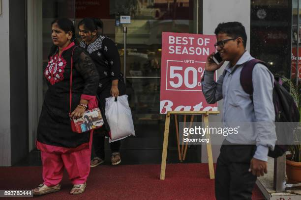 Shoppers walk past a sale sign displayed outside a store in Mumbai India on Friday Dec 15 2017 India's inflation surged past the central bank's...