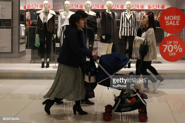 Shoppers walk past a sales sign at a shopping district in Tokyo Japan January 10 2018