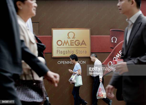 Shoppers walk past a sign advertising a new Omega store to be opened in Causeway Bay Hong Kong China on Monday November 20 2006 Hong Kong's retail...