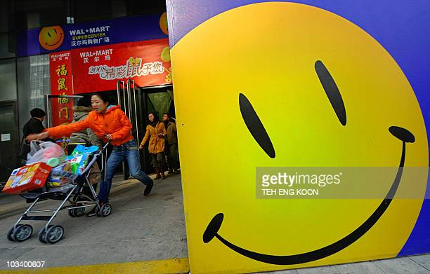 Shoppers walk past a smiling sign displayed at a WalMart hypermarket in Beijing on February 21 2008 With millions of consumers at stake global retail...