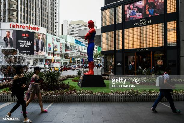 Shoppers walk past a SpiderMan statue installed to promote the franchise's latest film 'SpiderMan Homecoming' at a shopping mall in Kuala Lumpur on...