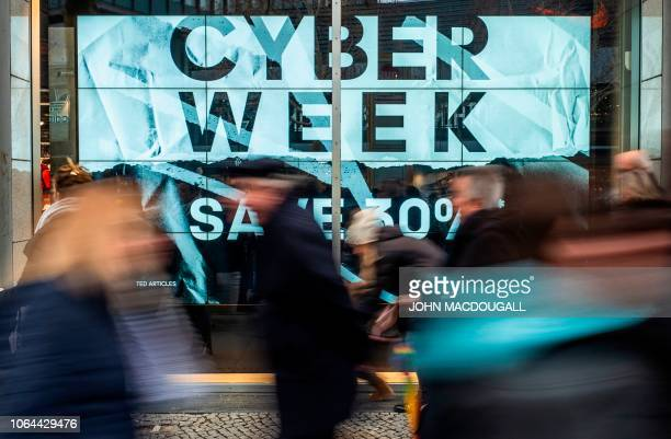 """Shoppers walk past a store advertising a so-called """"Cyber Week"""" sale, in Berlin on November 23, 2018. - """"Cyber Monday"""" marks the Monday after the..."""