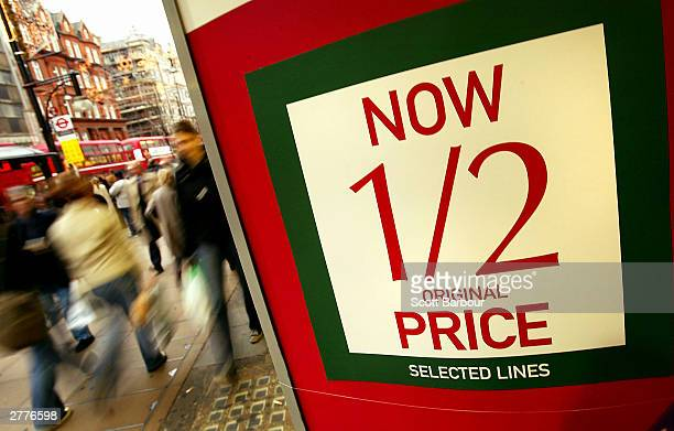 Shoppers walk past a store advertising items for half price December 2 2003 in London England A survey has found that a third of British Christmas...