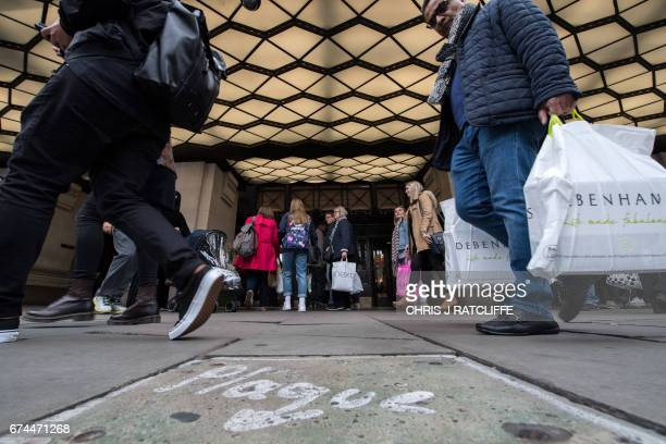 Shoppers walk past a store on Oxford Street in London on April 28 2017 Global stock markets went soft on April 28 weighed down by disappointing...