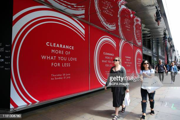 Shoppers walk past a store window display on Oxford Street as summer sales begin Many departmental stores are offering huge discounts as they face...