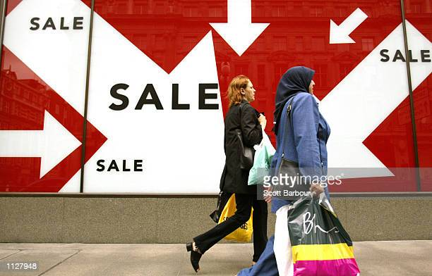 Shoppers walk past a store window during the 'Summer Sale' event July 7 2002 in London England The sale period entices costomers with deep discounts