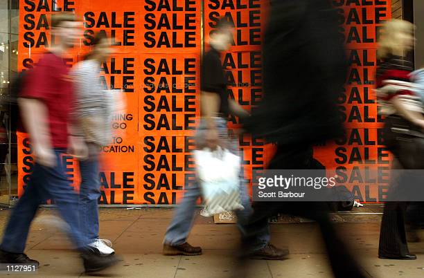 """Shoppers walk past a store window during the """"Summer Sale"""" event July 13, 2002 in London, England. The sale period entices costomers with deep..."""