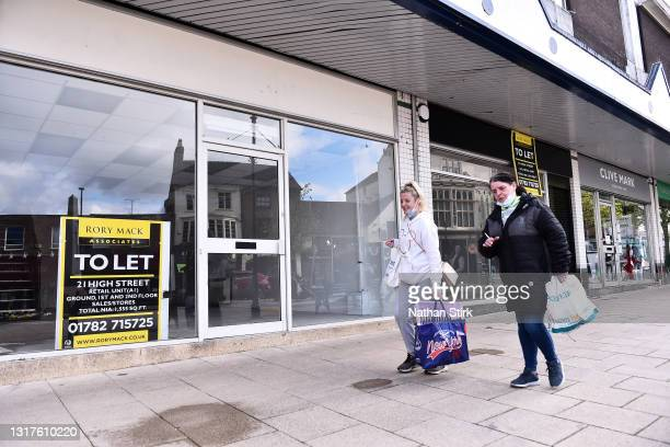Shoppers walk past an empty shop which displays a 'To Let' sign in the window on May 12, 2021 in Newcastle-Under-Lyme, England.