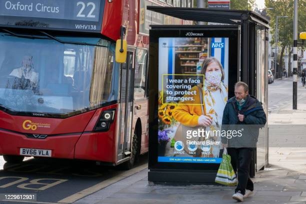 Shoppers walk past an NHS bus shelter ad on the King's Road during the second lockdown of the UK's Coronavirus pandemic, when all but essential...