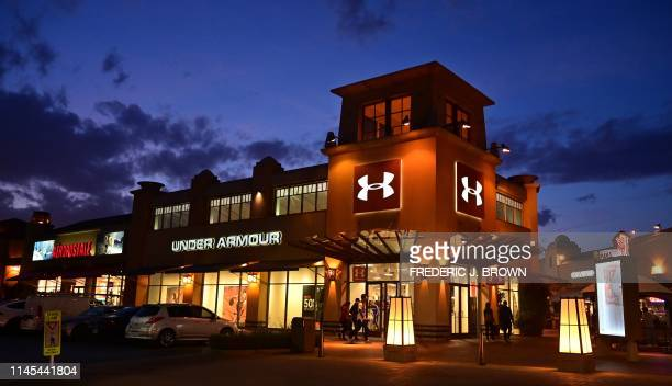 Shoppers walk past an Under Armour store at an outlet mall in Los Angeles on May 21 2019 More than 170 shoe companies and retailers including Adidas...