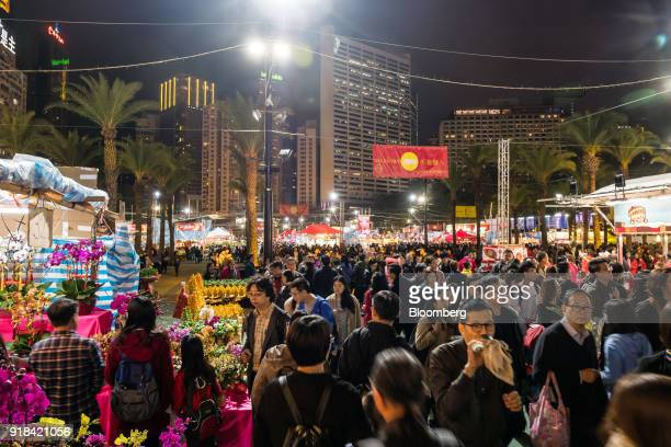 Shoppers walk past flower stalls at the Lunar New Year fair at Victoria Park in Hong Kong China on Wednesday Feb 14 2018 The city's financial markets...