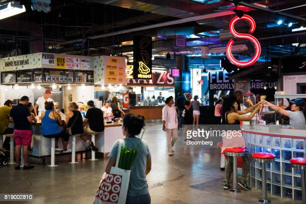 Shoppers walk past food stands inside DeKalb Market Hall at City Point in the Brooklyn borough of New York US on Tuesday July 18 2017 Bloomberg is...