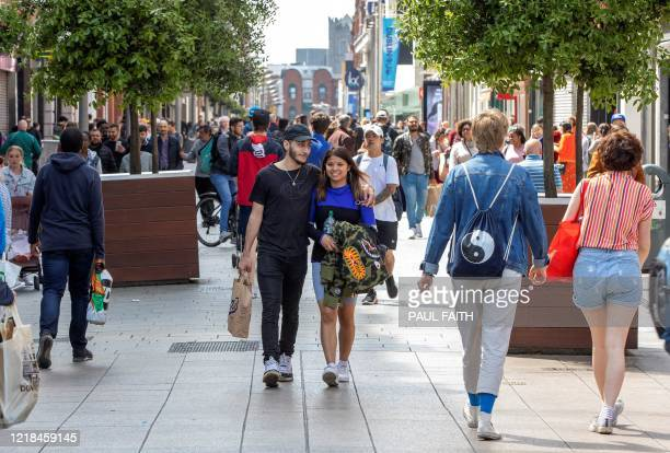 Shoppers walk past re-opened shops and businesses on O'Connell Street in central Dublin, Ireland on June 8 as lockdown measures are eased during the...