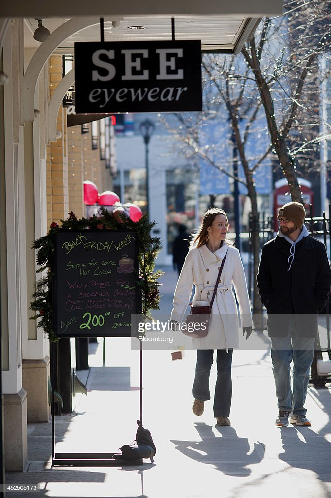 Shoppers walk past store fronts at the Easton Towne Center in Columbus, Ohio, U.S., on Friday, Nov. 29, 2013. About 97 million people planned to shop online or in stores on Black Friday, with about 140 million intending to do so yesterday through Sunday, the National Retail Federation said. Photographer: Ty Wright/Bloomberg via Getty Images