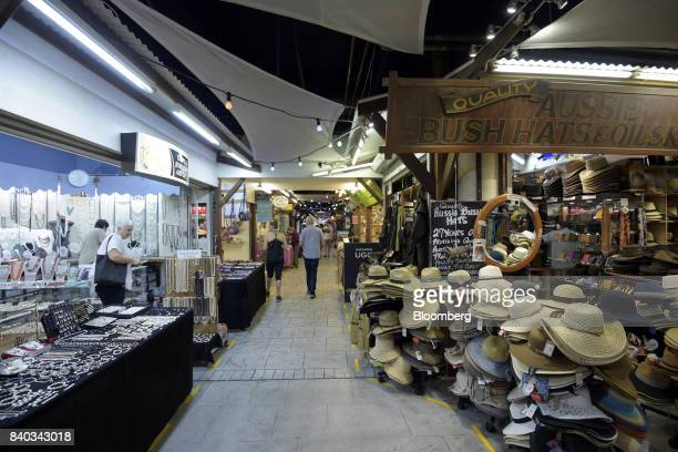 Shoppers walk past stores at a market in Cairns Australia on Monday July 31 2017 Australia's stocks and bonds are rallying in August and economic...