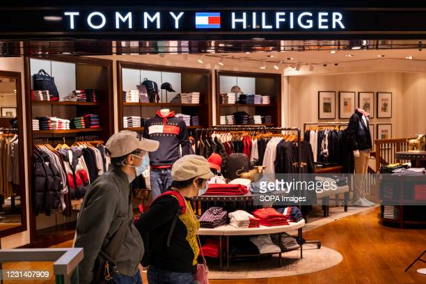 Shoppers walk past the American multinational clothing fashion brand, Tommy Hilfiger store seen in Hong Kong.