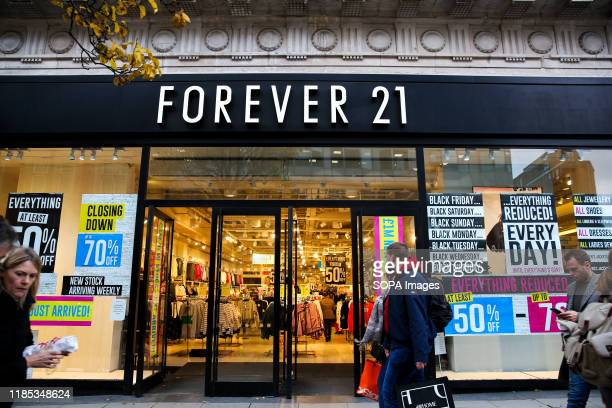 Shoppers walk past the Closing Down signs in the window of Forever 21 store on Oxford Street in London.