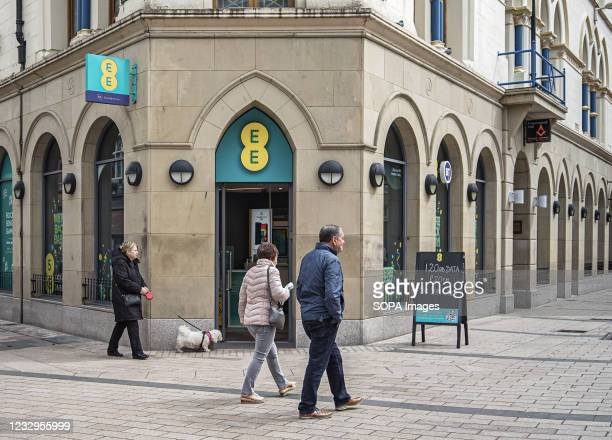 Shoppers walk past the EE Mobile Phone Store.