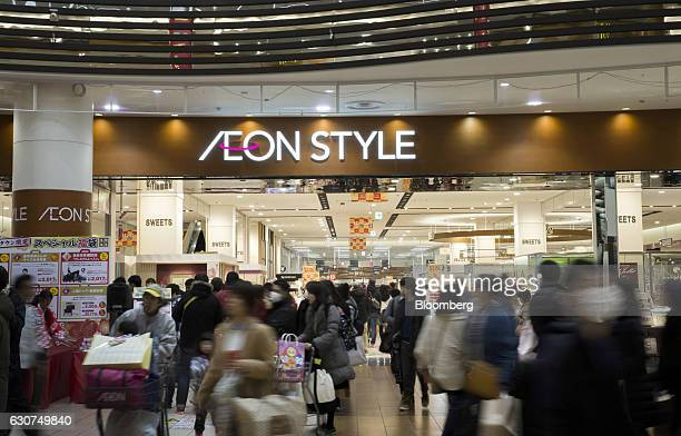 Shoppers walk past the entrance to an Aeon Style store at the Aeon Lake Town shopping mall operated by Aeon Retail Co a unit of Aeon Co on the first...