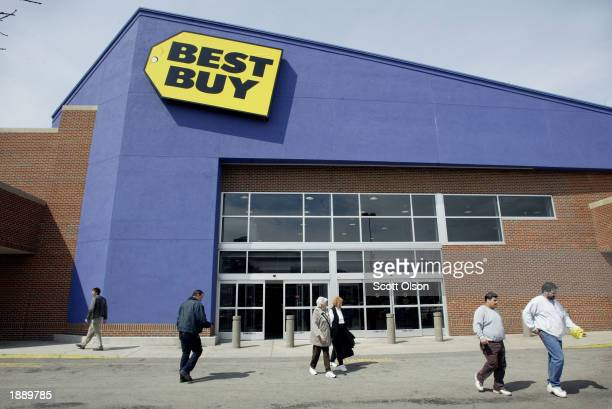 Shoppers walk past the front of a Best Buy store April 1 2003 in Chicago Best Buy announced lower fourth quarter earnings earlier in the day and also...