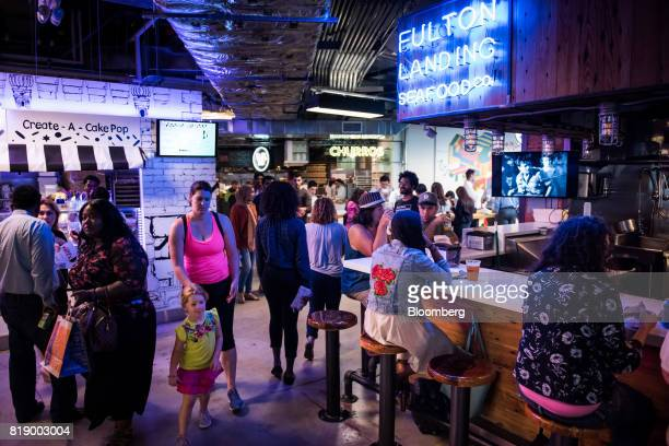 Shoppers walk past the Fulton Landing Seafood Co stand inside DeKalb Market Hall at City Point in the Brooklyn borough of New York US on Wednesday...