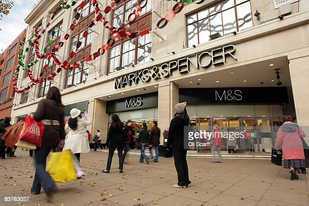 Shoppers walk past the Marks and Spencer department store on Oxford Street which is holding a '20% Off Everything' sale on November 20 2008 in London...