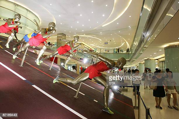 Shoppers walk past various display of 2008 Beijing Olympic Games jerseys and uniforms at a shopping mall in Beijing August 6 2008 Beijing is...