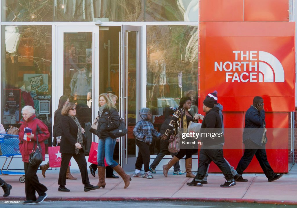 Shoppers walk the North Face at the Easton Towne Center in Columbus, Ohio, U.S., on Friday, Nov. 29, 2013. About 97 million people planned to shop online or in stores on Black Friday, with about 140 million intending to do so yesterday through Sunday, the National Retail Federation said. Photographer: Ty Wright/Bloomberg via Getty Images