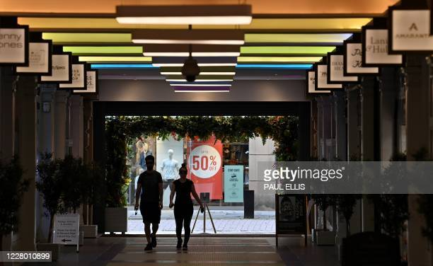 Shoppers walk though an empty shopping centre in Manchester northern England on August 12 2020 Britain's economy contracted by a record 204 percent...