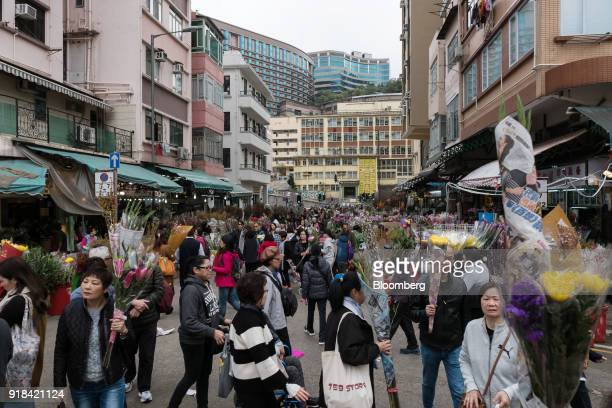 Shoppers walk through a flower market ahead of Lunar New Year in the Mong Kok district of Hong Kong China on Wednesday Feb 14 2018 The city's...