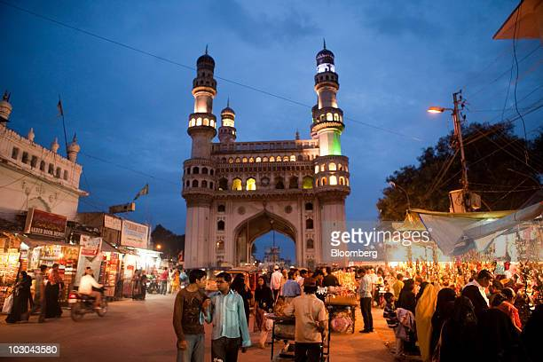 """Shoppers walk through a market adjacent to the """"Char Minar"""" monument in Hyderabad, India, on Wednesday, July 21, 2010. India's gross domestic product..."""