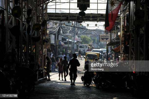 Shoppers walk through a market during a partial lockdown imposed due to the coronavirus in Quezon City, Metro Manila, the Philippines, on Wednesday,...