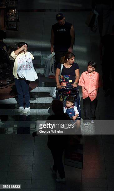 – Shoppers walk through a patch of sunlight comming in through the roof at the Northridge Fashion Center mall in Northridge today
