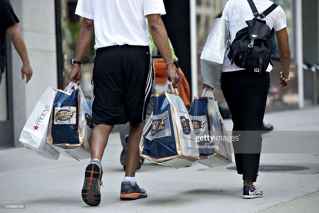 Shoppers walk through a retail area known as the 'Magnificent Mile' in Chicago, Illinois, U.S., on Tuesday, June 11, 2013. Sales at U.S. retailers probably rose in May as an improving job market gave consumers the confidence to shop for automobiles, home furnishings and clothing, economists said before reports this week. Photographer: Daniel Acker/Bloomberg via Getty Images