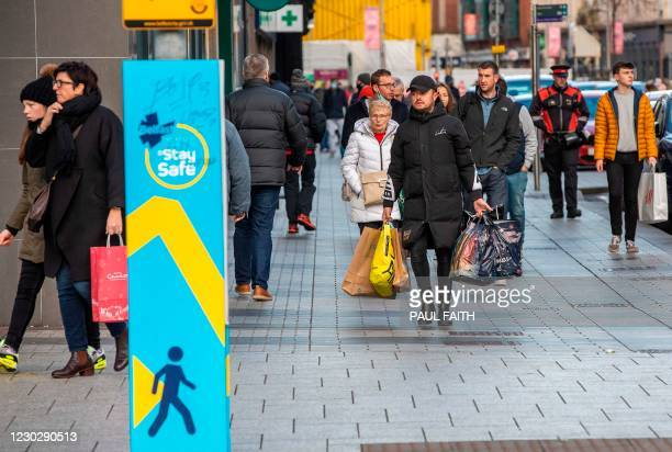 Shoppers walk through Belfast city centre on Christmas Eve, December 24, 2020 as the Province prepares to go into a six week lockdown. - Fears over...